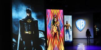 """A visitor walks past portraits of DC Comics superheroes as she enters the """"Action and Magic Made Here"""" interactive experience at the Warner Bros. Studio Tour Hollywood media preview in Burbank, Calif.                                  AP photo"""