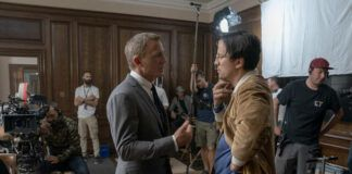 """This mage released by MGM shows director Cary Joji Fukunaga, right, with actor Daniel Craig on the set of the James Bond film """"No Time to Die."""" (Nicola Dove/MGM via AP)"""